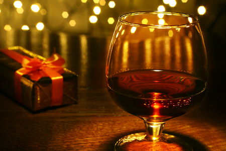 Photo for Whiskey, cognac, brandy and gift box on wooden table. Celebration composition on the light background. - Royalty Free Image