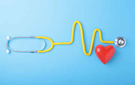 Photo pour Red heart and a stethoscope on blue background - image libre de droit