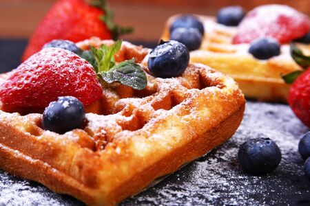Photo for Homemade Traditional belgian waffles with fresh fruit, berries and sugar powder on black plate. - Royalty Free Image