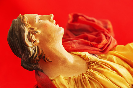 Photo for Wooden head of an angel in a religion ecstasy ,the angel is turned sideways , sweet and beautiful face ,the cloth is yellow and red , the backgrouns is red and out of focus - Royalty Free Image
