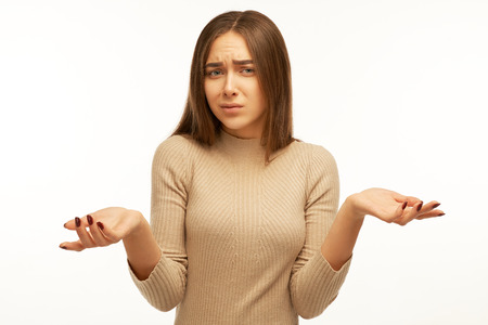 Foto de Young female with hesitant expression, shruggs shoulders and keeps palms raised, has clueless look, isolated over white studio background. Puzzlement and doubt concept. - Imagen libre de derechos
