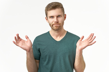 Foto de Confused young man spreads hands in different sides, feels uncertain, wears casual t shirt. Being puzzled by unexpected event, poses over white blank studio wall. - Imagen libre de derechos