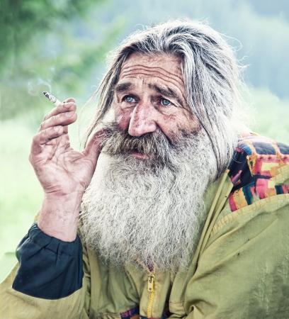 Photo pour portrait of smoking old man with gray beard  - image libre de droit