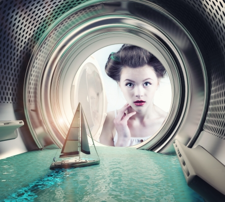 Photo pour Girl surprised yacht in the washing machine (creative concept) - image libre de droit