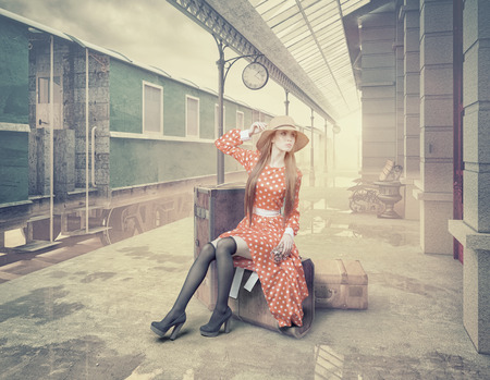 Photo for The girl sitting on the suitcase waiting at the retro railway station. Vintage color cards style - Royalty Free Image