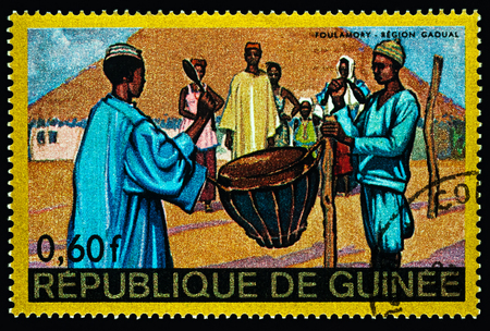Foto de Moscow, Russia - February 28, 2018: A stamp printed in Guinea shows scene of traditional native life in African village, Foulamory, Gaoual Region, series Regional Costumes and Habitations, circa 1968 - Imagen libre de derechos