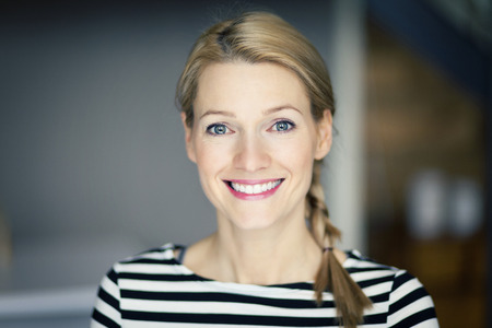 Photo for Smiling blond woman wearing a striped shirt - Royalty Free Image