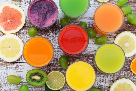 Foto de Glasses of tasty fresh juice, on wooden desk. Unusual top view - Imagen libre de derechos