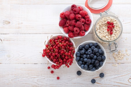 Photo for Summer breakfast. Ingredients for healthy breakfast - berries, fruit and muesli on white wooden table, close-up top view horizontal. Macro shot selective focus - Royalty Free Image