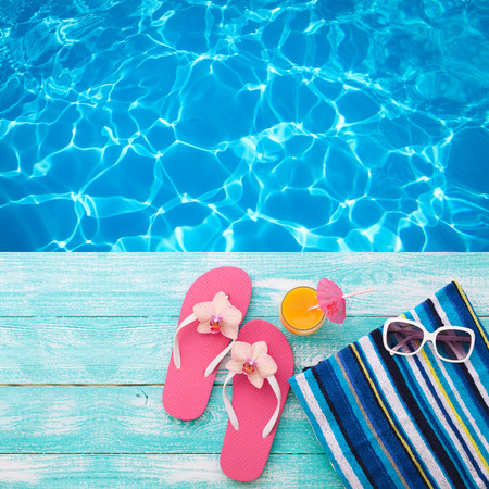 Photo for Summer Holidays in Beach Seashore. Summer drinks. Summer rest. Fashion accessories summer flip flops, hat, sunglasses on bright turquoise board near the pool - Royalty Free Image