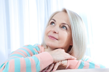 Foto per Attractive middle aged woman looking up relaxing at home. Beautiful face close up. - Immagine Royalty Free