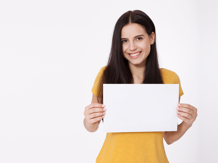 Photo pour Your text here. Pretty young woman holding empty blank board. Studio portrait on white background. Mockup for design - image libre de droit