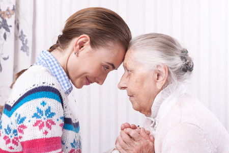 Foto de Helping hands, care for the elderly concept Senior and caregiver holding hands at home - Imagen libre de derechos