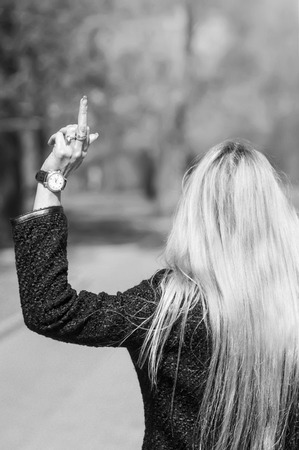 Photo pour Young blonde woman walking away showing her middle finger. In black and white - image libre de droit