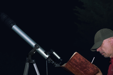 Photo for Man making drafting or drawing with a book in hands, sitting next to amateur telescope - Royalty Free Image