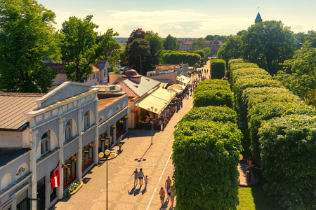 Photo for Pedestrians walk around Jomas Street in Jurmala, Latvia. The Jomas Street is the central and oldest street of Jurmala with restaurants, hotels and cafes. - Royalty Free Image