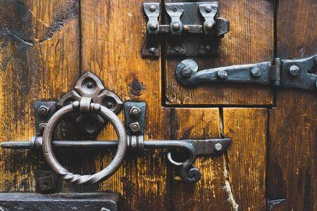 Photo pour Wooden door with antique wrought iron locks and bolts - image libre de droit