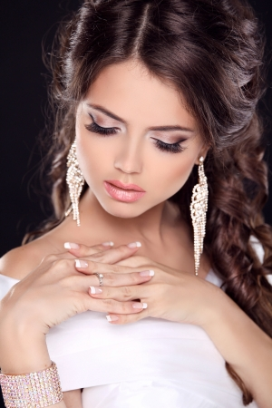 Beautiful young bride portrait in white dress. Fashion Beauty Girl. Make up. Jewelry. Manicured nails.