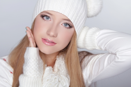 Beautiful teen girl wearing winter clothing and funny white hat. Isolated on grey background