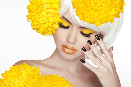 Photo for Beauty Blond Female Portrait with yellow flowers. Beautiful Spa Woman Touching her Face. Makeup and manicured nails. Perfect Fresh Skin. Isolated on white background - Royalty Free Image