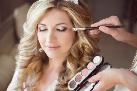 Foto de Beautiful bride girl with wedding makeup and hairstyle. Stylist makes make-up bride on wedding day. portrait of young woman at morning. - Imagen libre de derechos