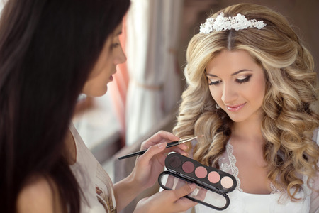 Foto de Beautiful bride wedding with makeup and hairstyle. Stylist makes make-up bride on wedding day. portrait of young woman at morning. - Imagen libre de derechos