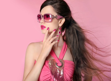 Photo pour Beauty fashion model girl in sunglasses with bright makeup, long hair, manicured nails. Glamour woman isolated on pink studio background. - image libre de droit