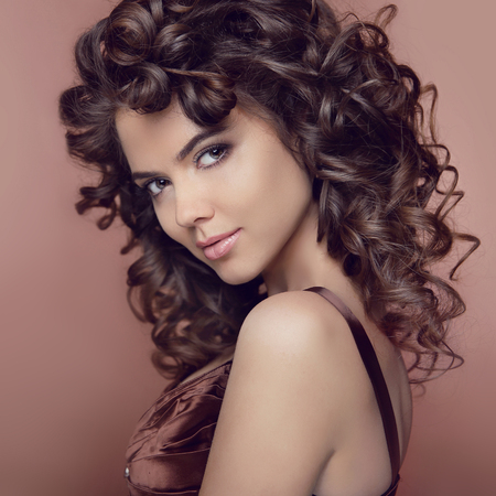 Photo for Wavy hair. Attractive smiling girl with makeup. Curly hairstyle. Brunette. Expressive eyes stare. Elegant lady over studio beige background. Luxury vogue style - Royalty Free Image