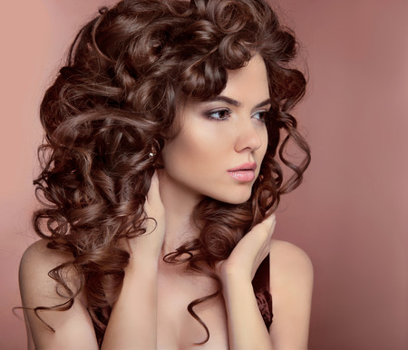 Photo pour Wavy hair. Beautiful girl with makeup. Curly hairstyle. Brunette. Expressive eyes stare. Fashion young woman isolated on  studio beige background. Luxury vogue style - image libre de droit