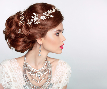 Foto de Wedding Hairstyle. Beautiful fashion bride girl model portrait. Luxury jewelry.  Attractive young woman with red hair. - Imagen libre de derechos