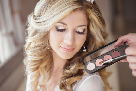 Foto de Beautiful bride wedding with makeup and curly hairstyle. Stylist makes make-up bride on wedding day. Beauty portrait of young woman at morning. - Imagen libre de derechos