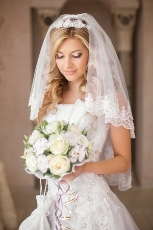 Foto de Beautiful bride woman with bouquet of flowers, wedding makeup and hairstyle, bridal veil. Girl wearing in white wedding dress posing. indoor portrait. - Imagen libre de derechos
