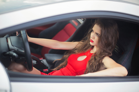 Photo pour Beautiful girl driver driving in car, sensual brunette model wearing in red dress sitting in automobile. - image libre de droit