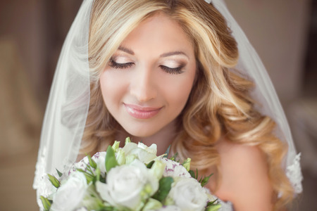 Foto de Beautiful bride with wedding bouquet of flowers. Makeup. Blond curly hairstyle. Smiling young woman. - Imagen libre de derechos