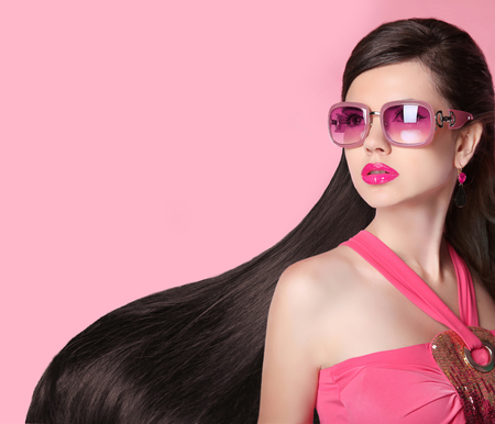 Foto de Hair. Beautiful Brunette Girl. Healthy Long Hairstyle. Fashion  sunglasses. Beauty Model Woman. Glamour female person isolated on pink studio background. - Imagen libre de derechos