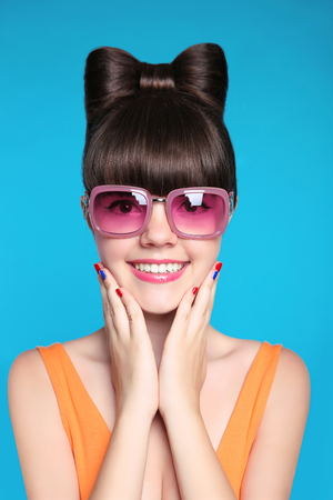 Photo pour Happy smiling teen girl with bow hairstyle, funny model wearing in fashion pink sunglasses isolated in blue background. - image libre de droit