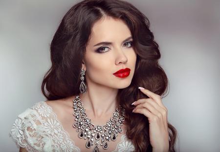 Foto de Portrait of a beautiful fashion bride girl with sensual red lips. Wedding make up and waving hair. Studio background. Luxury modern style. - Imagen libre de derechos