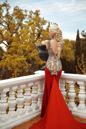 Sexy back young beauty woman in mermaid red dress. gorgeous fashion blond girl model with long curly elegant hairstyle. outdoor autumn portrait.
