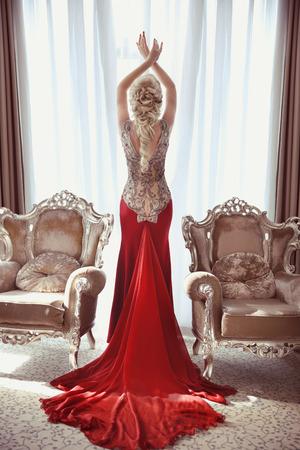 Foto de Indoor full length portrait of elegant blond woman in red gown with long train of dress posing between two modern armchairs in front of window at interior. - Imagen libre de derechos