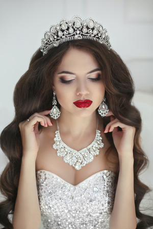 Photo pour Beautiful bride makeup, fashion jewelry. Elegant brunette woman with long wavy hair style and red lips makeup in wedding dress posing in white interior. - image libre de droit