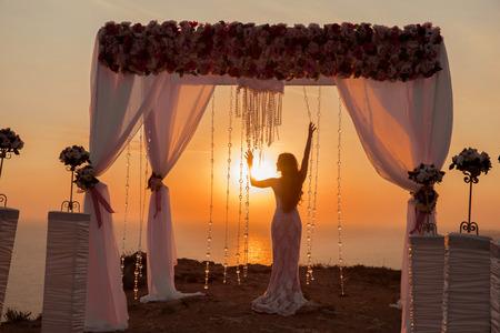 Photo pour bride silhouette. Wedding ceremony arch with flower arrangement with white curtain at sunset above sea, outdoor photo. decor. - image libre de droit