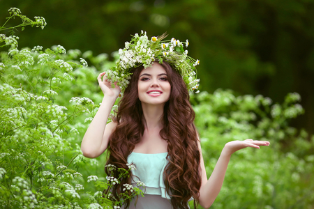 Photo for Portrait of smiling young woman in green spring park with open empty palm hand for copy space. Beautiful female with healthy long curly hair posing outdoors. - Royalty Free Image