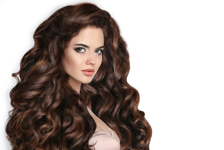 Photo pour Brunette. Long hair. Curly hairstyle. Beautiful woman with wavy healthy hair isolated on studio white background. Beauty makeup. Shampoo healthcare. Stare. - image libre de droit