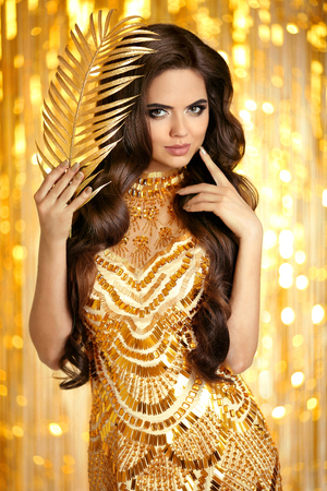 Foto de Elegant brunette in golden sparkling dress. Fashion Glamour style. Beauty makeup and wavy hairstyle. Beautiful smiling woman with long hair style posing over gold bokeh lights background. - Imagen libre de derechos