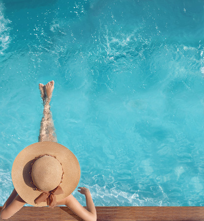 Foto de Back view of woman in straw hat relaxing in turquoise water swimming pool at luxury villa resort. Summer holiday idyllic background. Vacations Concept. Exotic Paradise. - Imagen libre de derechos