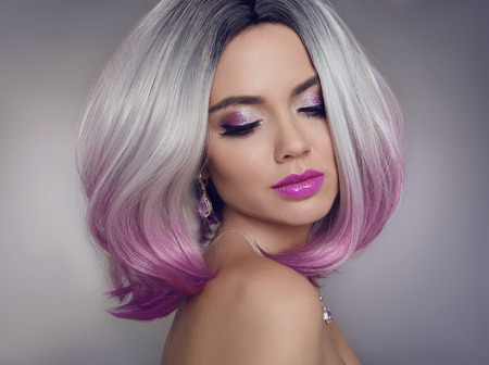 Foto de Colored Ombre hair extensions. Beauty Model Girl blonde with short bob purple hairstyle isolated on gray background. Closeup woman portrait. - Imagen libre de derechos