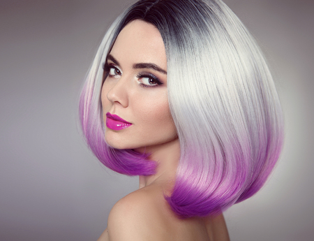 Foto de Bob hairstyle. Colored Ombre hair extensions. Beauty Model Girl blonde with short purple hair style isolated on gray background. Closeup woman portrait. - Imagen libre de derechos