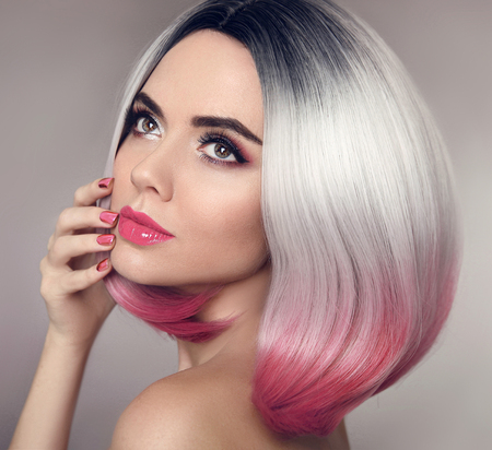 Foto de Colored Ombre bob hair extensions. Manicure nails. Beauty makeup. Attractive Model Girl blonde with short pink hairstyle isolated on gray background. Closeup woman portrait. - Imagen libre de derechos