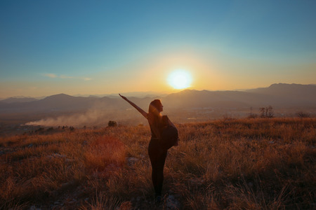 Foto de Sunset mountain. Tourist Free happy  woman outstretched arms with backpack enjoying life in wheat field. Hiker cheering elated and blissful with arms raised at sunrise. - Imagen libre de derechos