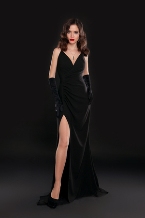 Foto de Elegant lady in long sexy dress with retro wavy hairstyle posing isolated on studio black background. Beautiful brunette woman in glamour gloves. Fashion style full length photo. - Imagen libre de derechos